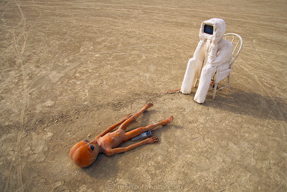 Art installation at Burning Man. Black Rock Desert, Nevada: Art installation with TV head watching alien crash victim body. Burning Man is a performance art festival known for art, drugs and sex. It takes place annually in the Black Rock Desert near Gerlach, Nevada, USA.