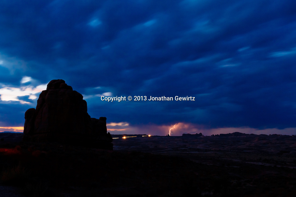 Lightning from a distant storm and headlights on the main park road illuminate  rock formations in this long-exposure view of Arches National Park, Utah. WATERMARKS WILL NOT APPEAR ON PRINTS OR LICENSED IMAGES.