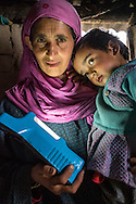 Amina, 38, holds a solar lamp while carrying her son Kheshboo, 3, in their collapsed house in Purnishadashah village, Jammu and Kashmir, India, on 24th March 2015. Amina's house was destroyed in the floods forcing her to move in with relatives. Save the Children supported them with kitchen items, hygiene kits, food baskets, blankets, a solar powered lamp and education kits for the children. Photo by Suzanne Lee for Save the Children
