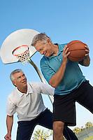 Senior men playing basketball on outdoor court