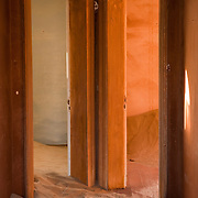 Two rooms at the end of a sand filled corridor in Kolmanskop, Namibia