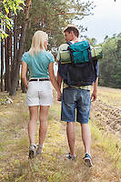Rear view of young hiking couple holding hands while walking in countryside