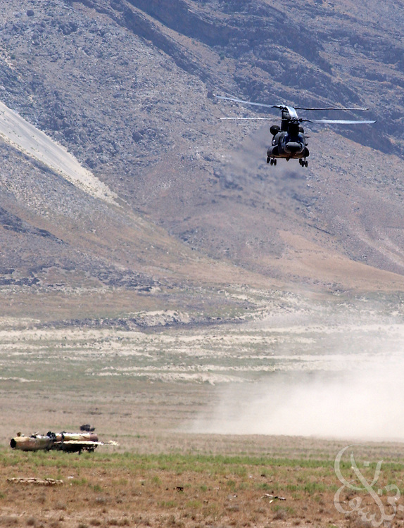 A U.S. Army CH-47 Chinook helicopter returns across the Shomali plain east of Bagram air base June 20, 2002 after having airlifted several scrap Russian MIG fighter jet bodies (bottom,L) and armored personnel carriers (APC) from a debris field on the base. The scrap equipment was air lifted to the plain for use as targets on a bombing range used to train troops deployed for Operation Enduring Freedom.