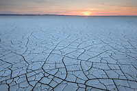 Setting sun on patterns of cracked mud on dry lakebed of Harney Lake, Malheur National Wildlife Refuge, Oregon