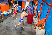 23 DECEMBER 2014 - BANGKOK, THAILAND: A boxer works a heavy bag in the Kanisorn gym in Bangkok. The Kanisorn boxing gym is a small gym along the Wong Wian Yai - Samut Sakhon train tracks. Young people from the nearby communities come to the gym to learn Thai boxing. Muay Thai (Muai Thai) is a mixed martial art developed in Thailand. Muay Thai became widespread internationally in the twentieth century, when Thai boxers defeated other well known boxers. A professional league is governed by the World Muay Thai Council. Muay Thai is frequently seen as a way out of poverty for young Thais. Muay Thai professionals and champions are often celebrities in Thailand.     PHOTO BY JACK KURTZ