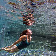 A mother swimming underwater while playing with her children in her back yard family swimming pool. Connecticut, USA. Photo Tim Clayton