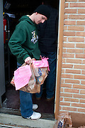 John Adams waits with a bag of donated food outside the St. Vincent food pantry on Stewart street during the Alpha Beta Psi food drive on February 23rd, 2012. Photo by: Ross Brinkerhoff.