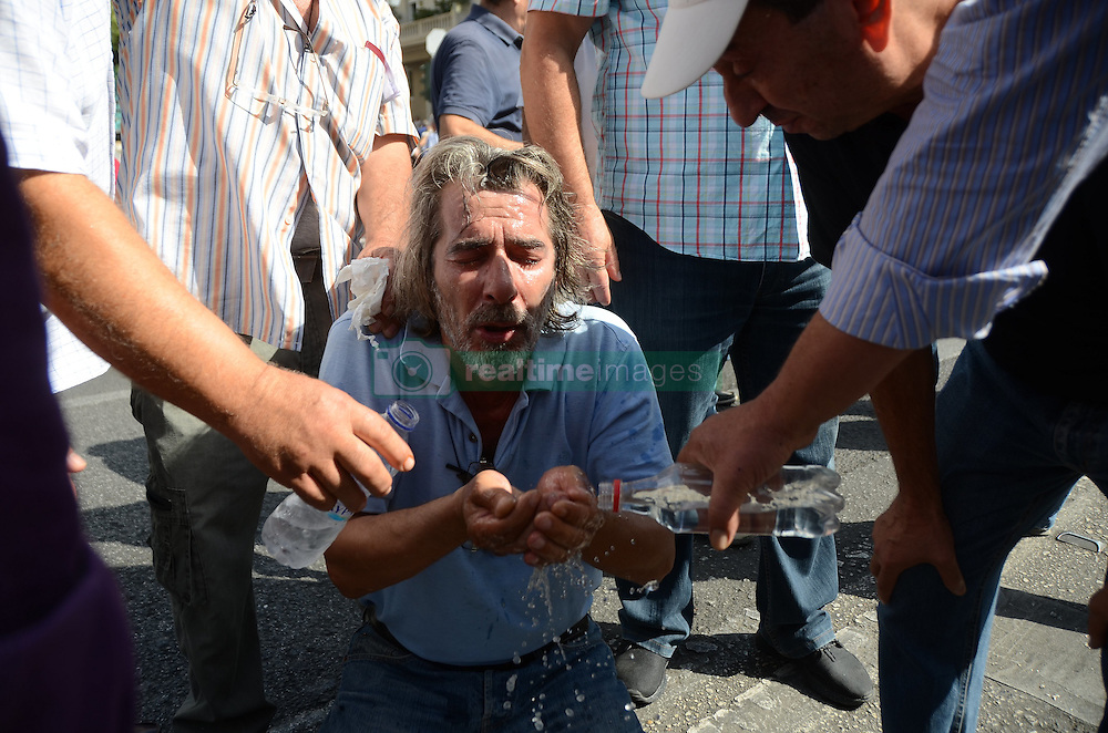 October 3, 2016 - Athens, Greece - Demonstrator that was hit by tear gas tries to avoid fainting and recieves aid..Greek pensioners demonstrate in Athens against the goverment cuts on pensions and their benefits in General. Demonstrators clashed with riot policve after they found the road to Prime Ministers office closed by police. (Credit Image: © George Panagakis/Pacific Press via ZUMA Wire)