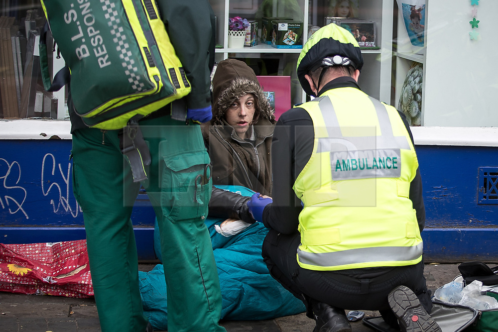 © Licensed to London News Pictures . 06/04/2017 . Manchester , UK . A bicycle paramedic responds to a call to help a woman , who is slouched and unresponsive in front of Max Spielmann photographic , in Piccadilly Gardens . An epidemic of abuse of the drug spice by some of Manchester's homeless population , in plain sight , is causing users to experience psychosis and a zombie-like state and is daily being witnessed in the Piccadilly Gardens area of Manchester , drawing large resource from paramedic services in the city centre . Photo credit : Joel Goodman/LNP