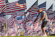 A man plays golf amongst 3,000 US flags are displayed at Pepperdine University to mark the 12th anniversary of the 9/11 terror attack, September 10, 2013 in Malibu, California. Photo by Ringo Chiu/PHOTOFORMULA.com)