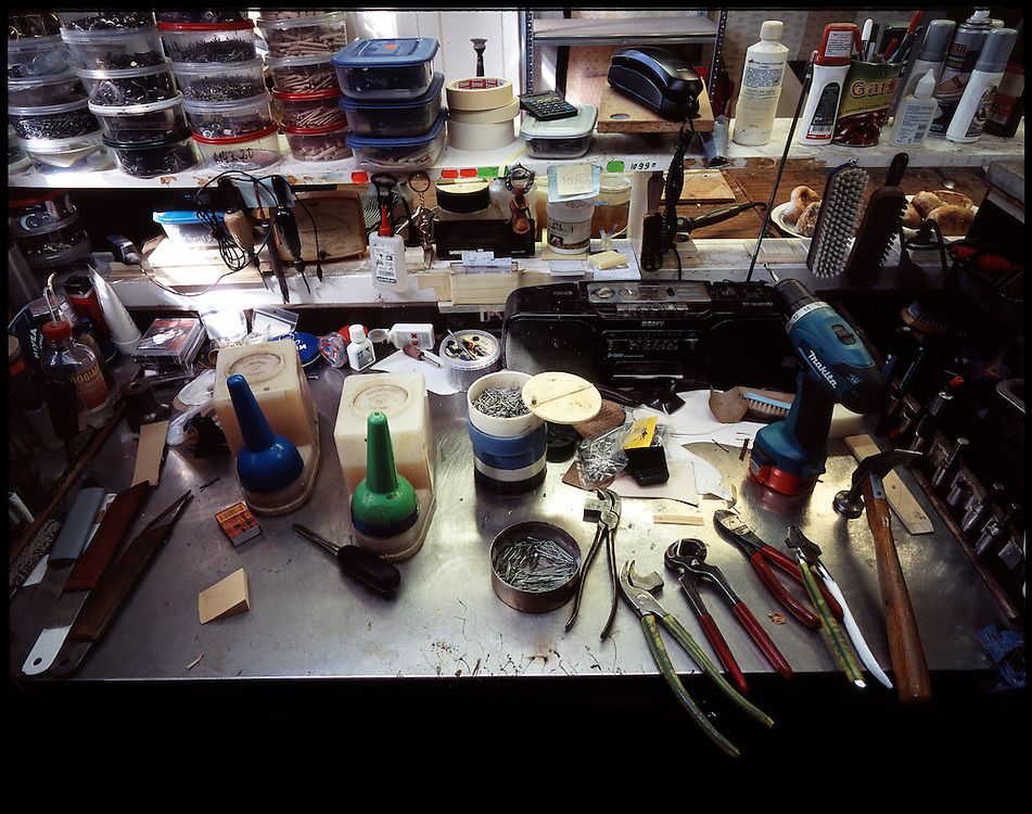 Shoemakers tools are arranged at the work desk in perfect order.
