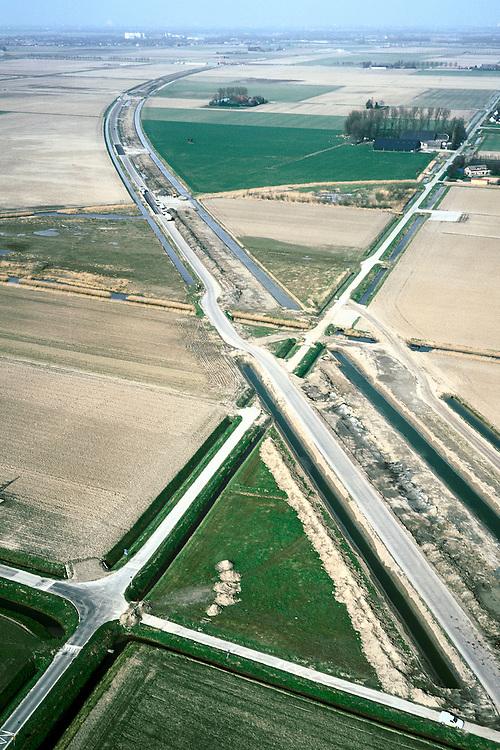 Nederland, Zuid-Holland, Hoeksche Waard, 08-03-2002;  het trace van de HSL (begint rechtsonder en buigt af naar de Oude Maas aan de horizon) vorm een litteken in het landschap; links van de werkweg een spoorsloot, rechts vd weg ruime voor de aardebaan en dn weer een spoorsloot; de diagonaal lopende Eerste Kruisweg wordt doorsneden, lokaal verkeer moet voortaan omrijden; infrastructuur verkeer en vervoer spoor bouw, landschap;<br /> luchtfoto (toeslag), aerial photo (additional fee)<br /> foto /photo Siebe Swart