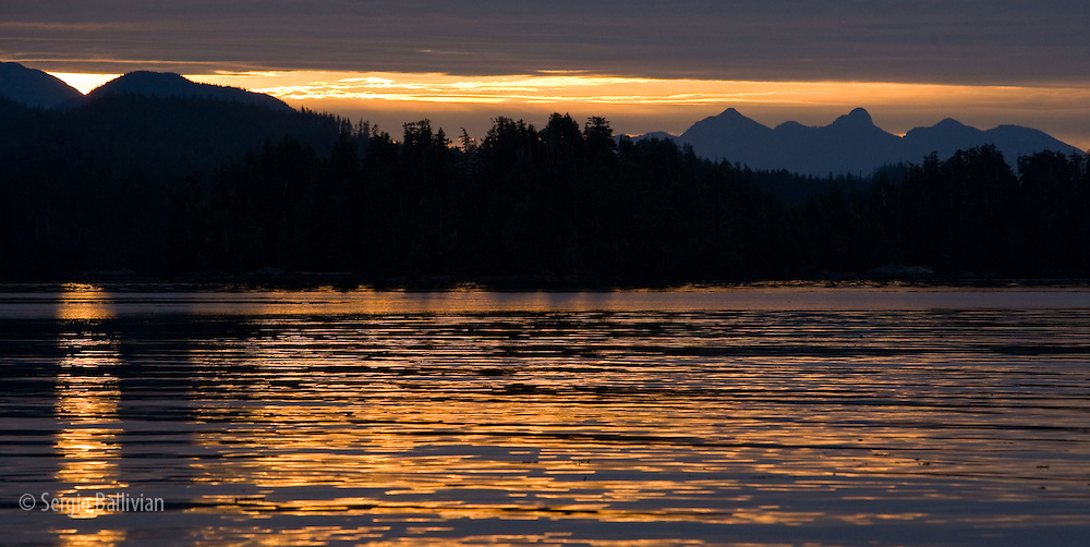 The warm orange colors of sunrise reveal calm waters and rugged mountains in Barkley Sound, Vancouver Island, BC.
