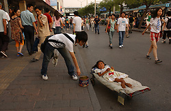 A handicapped child panhandles in Beijing, China. (Photo © Jock Fistick)