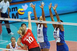 Belgium Lise Van Hecke spikes against Ocasio's sisters block