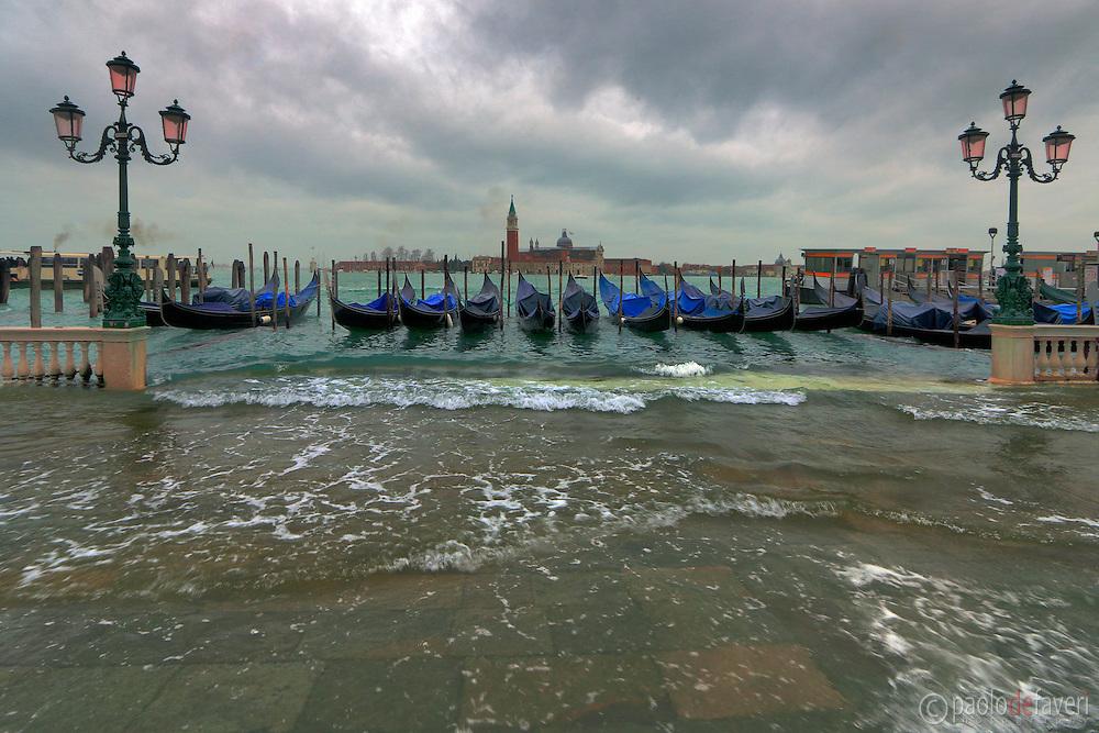 Gondolas at Riva degli Schiavoni in Venice, Italy, waving in the exceptional high tide (Acqua Alta) that occasionally floods Venice in winter time