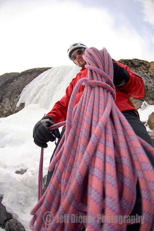 A young man coils a rope after ice climbing in Hyalite Canyon near Bozeman, Montana.