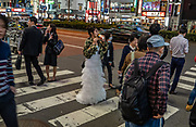Woman in wedding dress sips a soda in Kabukicho entertainment and neon red-light district in Shinjuku ward, Tokyo, Japan. Kabukicho was named from late-1940s plans to build a kabuki theater which never happened.