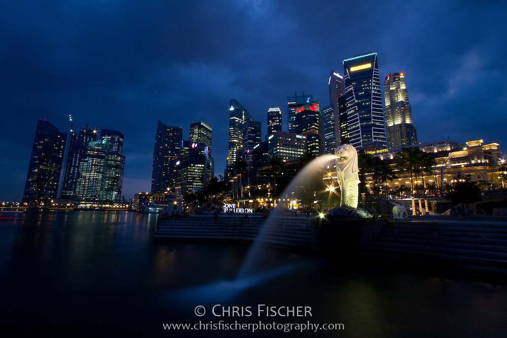 Singapore skyline at dusk, with the Merlion statue in the foreground.
