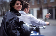 A man and woman on a motorbike. Woman is sitting on the backseat and is looking back into the camera, UK 2004