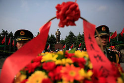 A picture made available on 12 May 2016 of Mao Zedong's giant statue seen behind flower wreaths carried by People's Liberation Army (PLA) soldiers on Mao Zedong Bronze Statue Square in Shaoshan, Hunan Province in central China, 28 April 2016. Shaoshan is the hometown of former Communist leader Mao Zedong, popularly known as Chairman Mao. As the fiftieth anniversary of the Cultural Revolution quietly approaches on 16 May, there is scant mention of the revolution where millions of intellectuals were persecuted and tortured in a bid to purge his critics in his this small town where he was hailed as a great hero and leader.