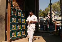Worshiper exits a temple in the Santhome district. Chennai is the third largest commercial and industrial centre in India. It is considered to be the automobile capital of India, with a major percentage of the country?s automobile industry having a base in the city. Chennai is the second-largest exporter of IT services in India, behind Bangalore and is a base for the manufacture of hardware and electronics, with many multinational corporations setting up plants in its outskirts. The city faces problems with water shortages, traffic congestion and air pollution.