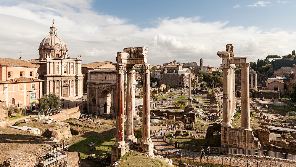 A view of ruins of Roman Forum in a sunny day. This is a major attraction in Rome and many tourists are visiting the archaeological site.