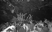 Crowd by a tree at outdoor rave, UK, 1980s.
