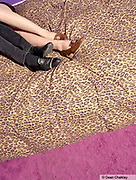 Legs of a couple on a bed with leopard print sheets, Southend, UK 2006