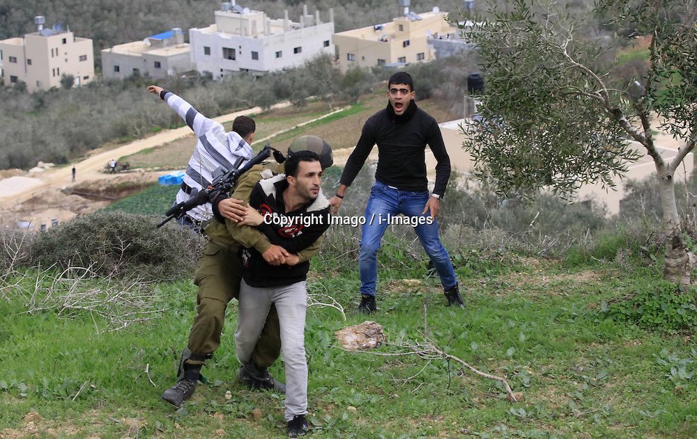 An Israeli soldier detains a Palestinian farmer from the northern West Bank village of Madama, December 17, 2012, Photo by Imago / i-Images...UK ONLY