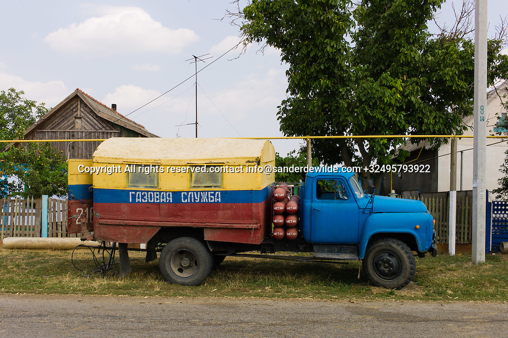 20150828  Moldova, Transnistria,Pridnestrovian Moldavian Republic (PMR) Frunze.A gas repair vehicle stands in front of a house with wooden rooftop. Rural Transnistrian village Frunze, east of Tiraspol is all agriculture.Gas tubes run overground, as seen as the yellow tube in the air.