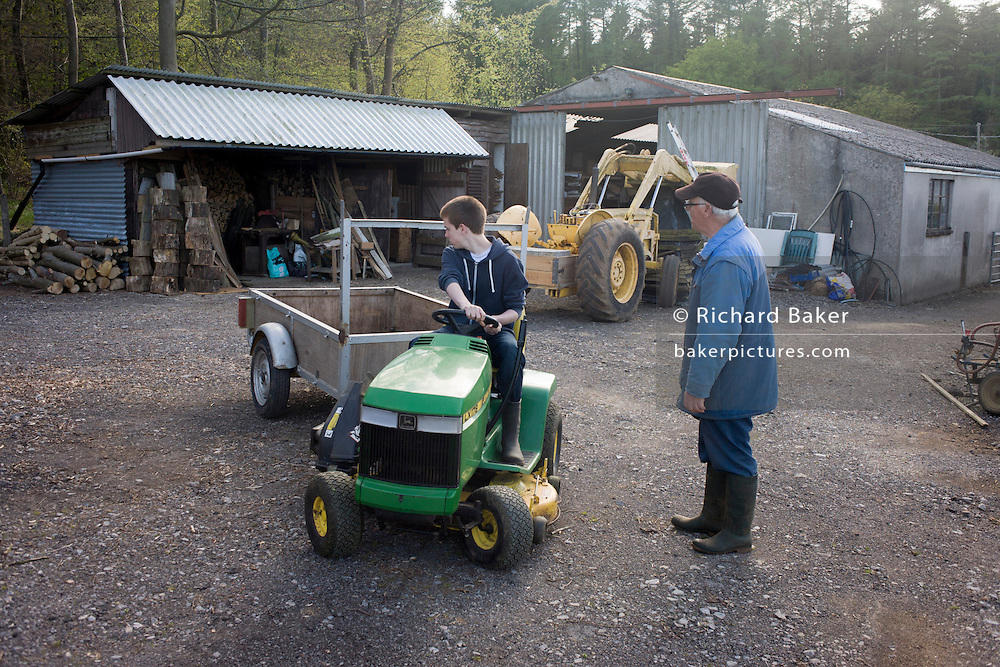 A teenage boy of 15 years of age learns the art of reversing a a small trailer on a family farmstead in north Somerset.