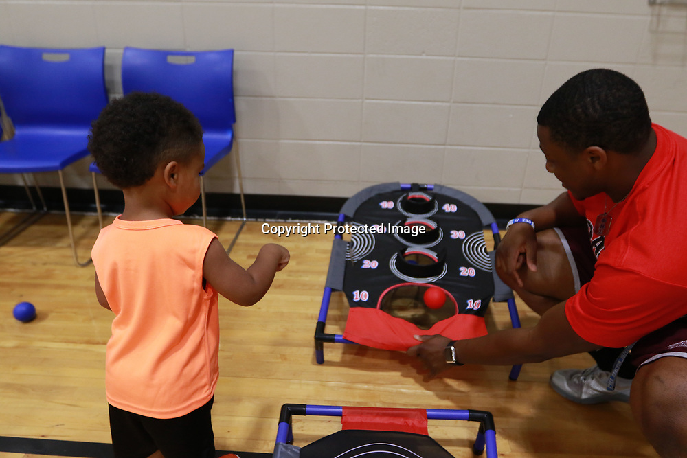 LIBBY EZELL | BUY AT PHOTOS.DJOURNAL.COM<br /> Tyler Armistad, right, helps P. J. Gordon, 2, make his ball go into the hole during Saturday's Police and Kid fun day
