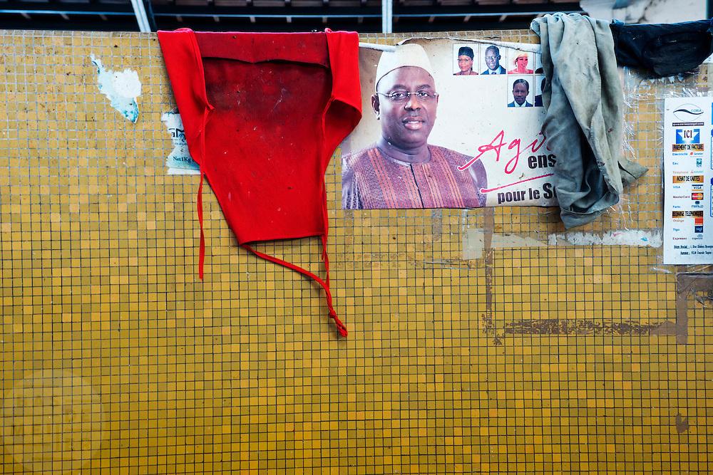 In de markthal van de Kemel markt in Dakar hangt een poster van de nieuwe president van Senegal.