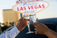 Two people toasting in front of  Welcome to Las Vegas sign