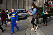A man wearing a bright Adidas tracksuit-type of sports clothing walks and talks passing the pillars of the Bank of England.