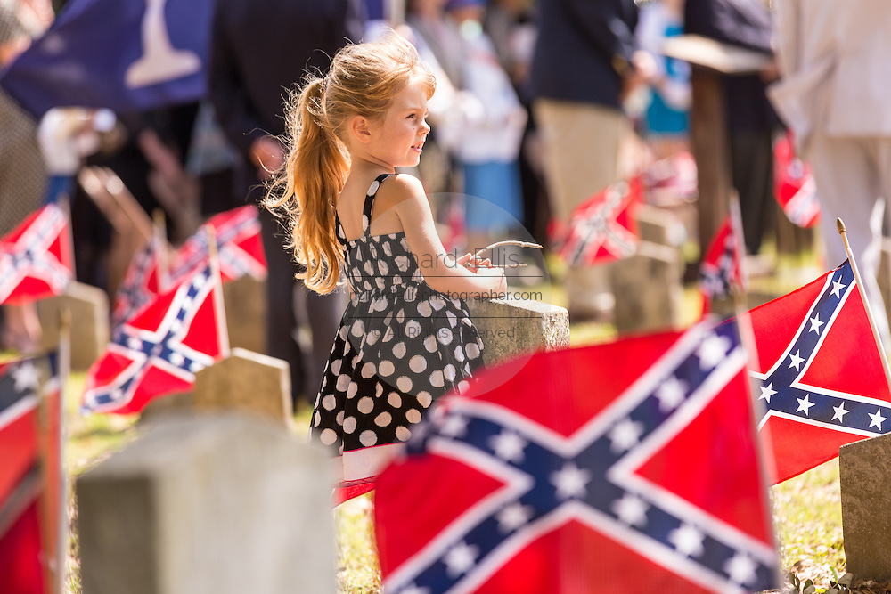 A young girl stands among Confederate flags decorating tombs of soldiers killed in the American Civil War during Confederate Memorial Day events at Magnolia Cemetery April 10, 2014 in Charleston, SC. Confederate Memorial Day honors the approximately 258,000 Confederate soldiers that died in the American Civil War.