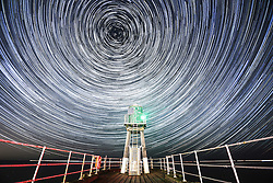 © Licensed to London News Pictures. 01/03/2017. Whitby UK. Picture shows star trails over the light house on Whitby sea defence in the early hours of this morning. Cloud cover cleared & left a crystal clear sky perfect for star gazing. Picture is a composite made up of 168 images taken over a one & a half hour period. Photo credit: Andrew McCaren/LNP