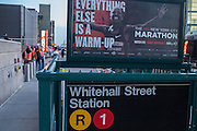 """A sign advertising the New York City Marathon, cancelled because of the storm, ironically states """"Everything else is a warm-up."""" MTA workers in safety vests can be seen in the distance, beyond the still closed Whitehall Street subway station."""