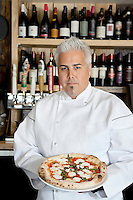 Portrait of a confident chef with pizza