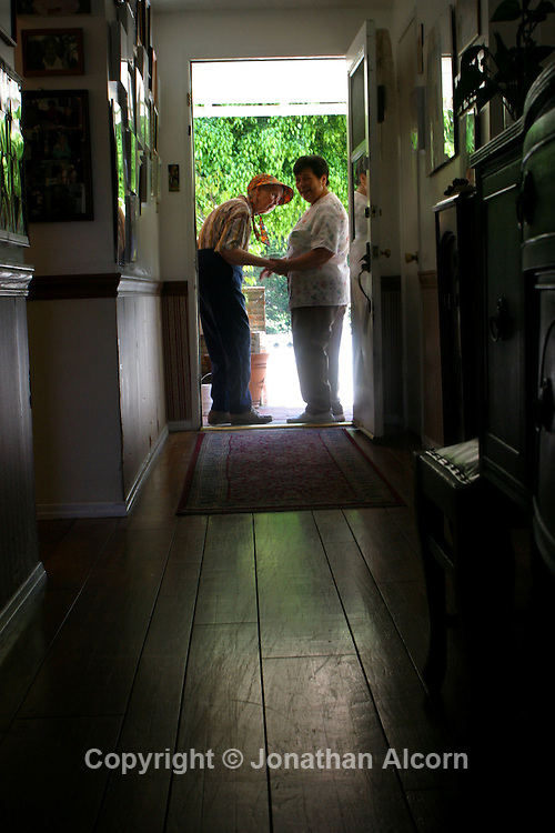 Healthcare worker takes an Alzheimer's patient  for a walk at a live-in residence for Alzheimer's and dementia related  patients.