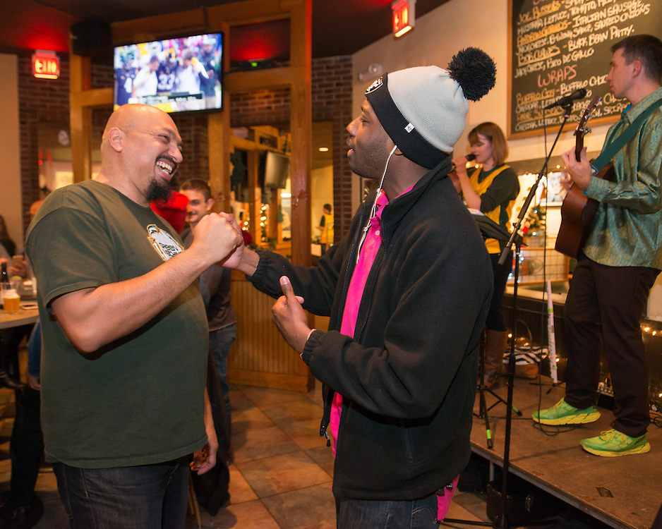 December 5, 2015 - Fairfax, VA - A day in the life of &quot;Doc Nix,&quot; aka Dr. Michael Nickens, the Director of the Athletic Bands for George Mason University. Here he jokes with a basketball player at the after game fete at Brion's Grille.<br /> <br /> <br /> Photo by Susana Raab