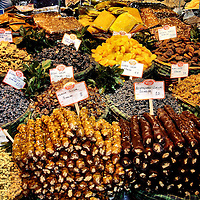 Candied Fruits on Display in Istanbul, Turkey<br /> You do not always know what you are eating when you travel to a foreign country, such as this display in Istanbul, Turkey, of different dried grapes, mulberries, legume seeds, apricots and plums plus curious, candy-covered sucuk (translated as sausages).  However, you always know you can pay for it with your Visa card or American Express as evidenced by those familiar logos in the upper-left corner.