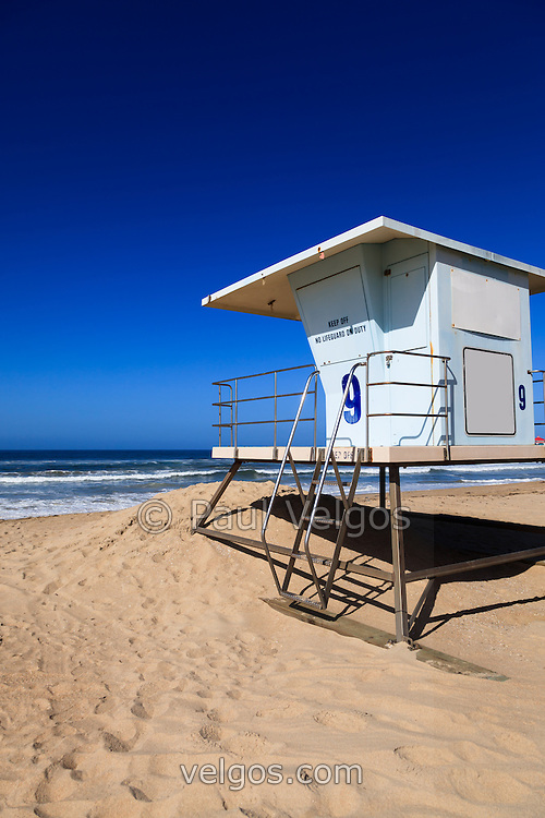 Photo of lifeguard tower #9 in Huntington Beach California. Huntington Beach is a seaside beach city in Orange County Southern California and is also known as Surf City USA. Photo has copy space for adding text.