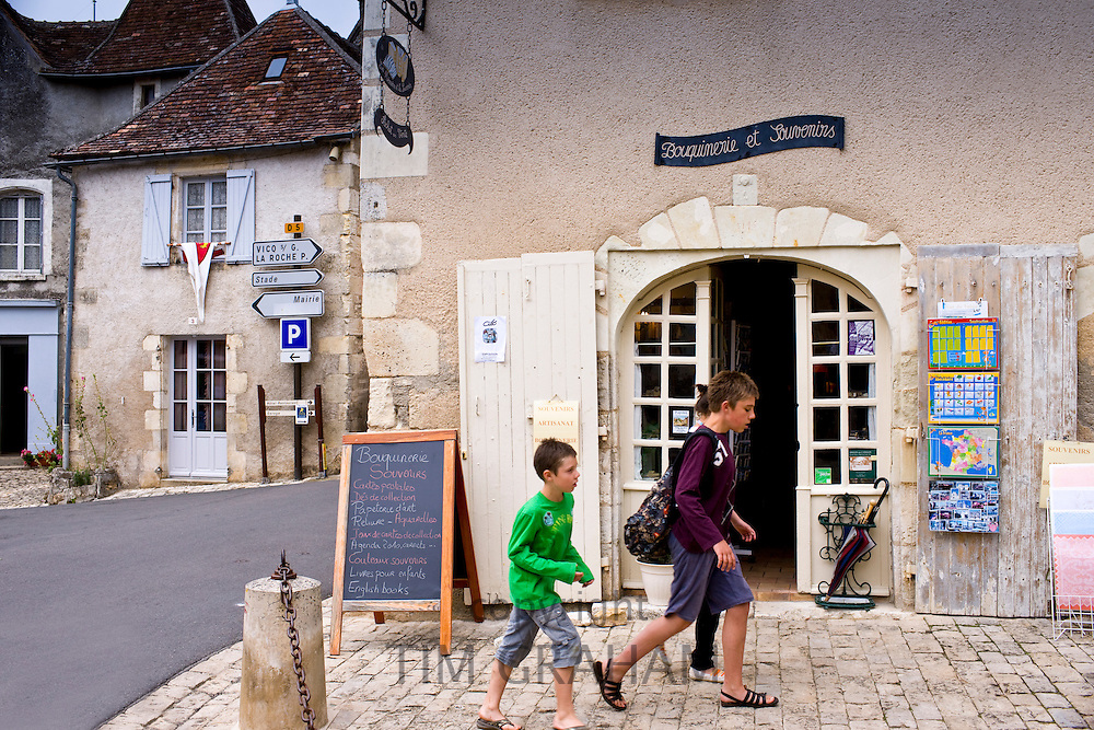 French children by souvenir shop in traditional French village of Angles Sur L'Anglin, Vienne, near Poitiers, France