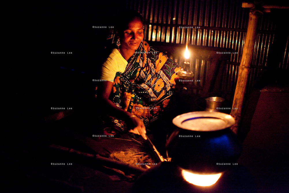 Shahida Begum, 35, cooks dinner in her home in Palashbari Villlage, Taragonj, Rangpur, Bangladesh on 18th September 2011. She has found financial independence and contributes to the family income by working as a saleswoman, earning 3500 - 5000 Bangladeshi Taka per month. She is one of many rural Bangladeshi women trained by NGO CARE Bangladesh as part of their project on empowering women in this traditionally patriarchal society. Named 'Aparajitas', which means 'women who never accept defeat', these women are trained to sell products in their villages and others around them from door-to-door, bringing global products from brands such as BATA, Unilever and GDFL to the most remote of villages, and bringing social and financial empowerment to themselves.  Photo by Suzanne Lee for The Guardian