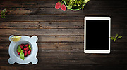 Mortar with fresh raspberries and basil, with customizable device, on wood background. Top view with copy space.