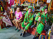 """26 NOVEMBER 2014 - BANGKOK, THAILAND:  Performers relax backstage during a Chinese opera at the Chow Su Kong Shrine in the Talat Noi neighborhood of Bangkok. Chinese opera was once very popular in Thailand, where it is called """"Ngiew."""" It is usually performed in the Teochew language. Millions of Chinese emigrated to Thailand (then Siam) in the 18th and 19th centuries and brought their culture with them. Recently the popularity of ngiew has faded as people turn to performances of opera on DVD or movies. There are about 30 Chinese opera troupes left in Bangkok and its environs. They are especially busy during Chinese New Year and Chinese holidays when they travel from Chinese temple to Chinese temple performing on stages they put up in streets near the temple, sometimes sleeping on hammocks they sling under their stage.     PHOTO BY JACK KURTZ"""