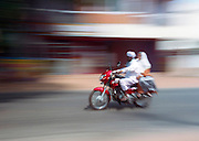 two people a man driving and a woman on the back seat side saddle,  on a motorbike with motion blur, India, Kerala, a state on the tropical coast of south west India