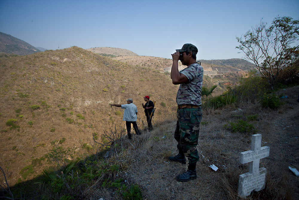 Community police members search the surrounding hills for remains of people murdered by cartels.
